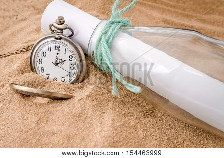 Vintage necklace watch on the sand beach