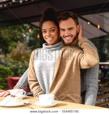 portrait of a cheery couple standing in front of a table with breakfast, selective focus