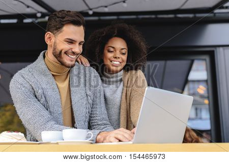 blogger with his girlfriend in front of laptop typing