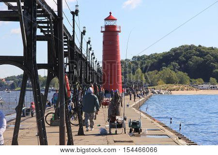 Crowds of people walk on the Grand Haven Breakwater and Lighthouse. Grand Haven, Michigan, Untied States - SEPTEMBER 12