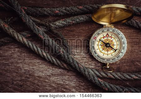 Old rope and compass on dark wooden background