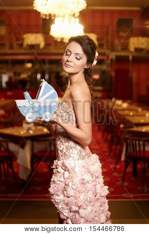 Beautiful bride in unusual wedding dress in the restaurant with perambulator
