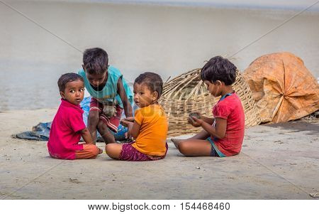 KOLKATA, INDIA - OCTOBER 8, 2016: Street children play with clay at Mallick Ghat, flower market, Kolkata, India. This ghat is located closest to the Howrah bridge on the bank of the river Ganges.