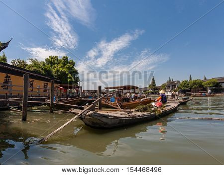ZHUJIAJIAO CHINA - AUGUST 30 2016: Boatman transports underwater grass by boat made of concrete on canal of ancient water town in Zhujiajiao China on August 30 2016.