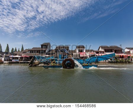 ZHUJIAJIAO CHINA - AUGUST 30 2016: Motorboat for cleaning underwater grass moves on canal of ancient water town with a history of more than 1700 years in Zhujiajiao China on August 30 2016.
