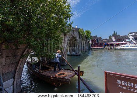 ZHUJIAJIAO CHINA - AUGUST 30 2016: Boatman transports Chinese tourist gondola under Fangsheng bridge on canal of ancient water town in Zhujiajiao China on August 30 2016.