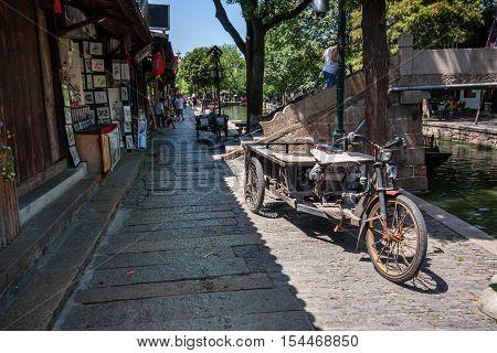 ZHUJIAJIAO CHINA - AUGUST 30 2016: Rusty three wheeled freight electric bike parked on canal embankment of ancient water town in Zhujiajiao China on August 30 2016.