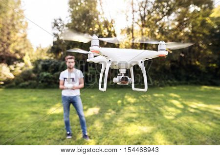 Young hipster man with remote control and flying drone with camera. Green sunny nature.