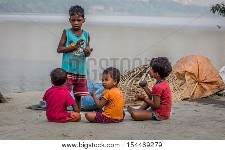 KOLKATA, INDIA - OCTOBER 8, 2016: Street kids play with clay at Mallick Ghat, flower market, Kolkata, India. This ghat is located closest to the Howrah bridge on the bank of the river Ganges.