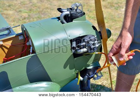Mechanic fueling the engine model military aircraft.