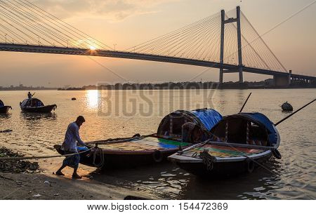 KOLKATA, INDIA - OCTOBER 29, 2016: Wooden country boats used for pleasure boat rides lined up at Princep Ghat on river Hooghly at sunset. The Hooghly river bridge at the backdrop.