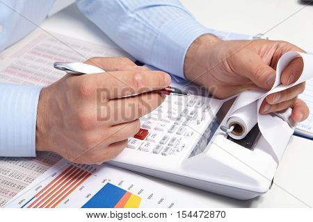 Businessman With Calculator In The Office