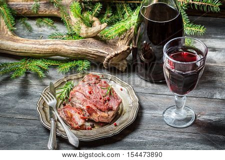 Red meat tastes best with wine on old wooden table