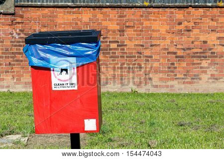 Red dog waste bin against a brick wall