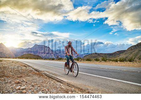 riding bike in nevada desert highway at sunset