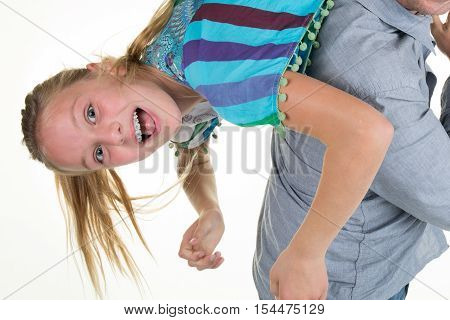 Father Playing With Happy Preteen Daughter, Holding Her Upside Down,