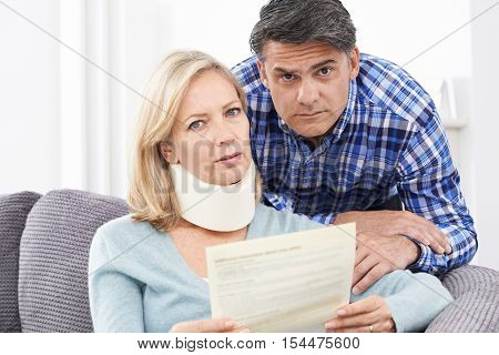 Portrait Of Couple Reading Letter About Woman's Injury