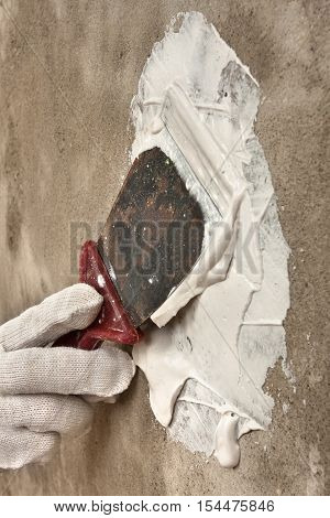 hand plastering concrete wall with putty knife during repair