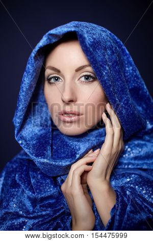 Beautiful woman closeup portrait bright makeup in blue color cloth isolated on dark