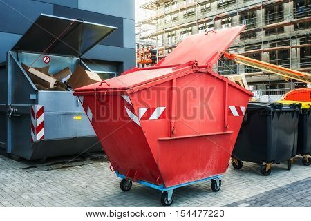 Red dumpster recycle waste and garbage bins near new office building. Construction site on background