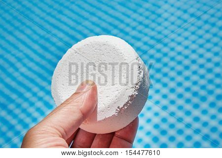 Hand Holding Chlorine Pellets With Inflatable Pool On Background