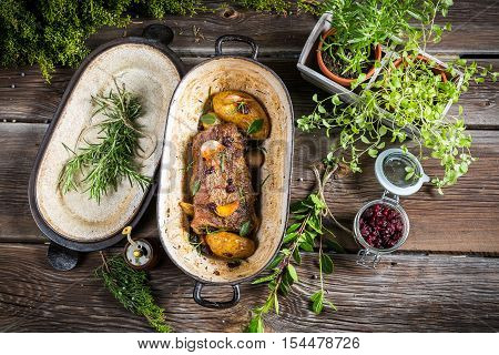 Roasted venison with herbs and vegetables on old wooden table