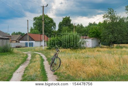 Ancient rusty bicycle waiting for the master on the roadside in rural village in Ukraine