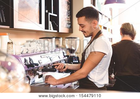 waist up of a bearded barista working with coffee making equipment