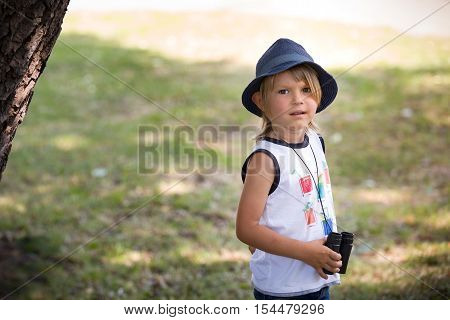Portrait of a cute kid boy with binoculars on a sunny day. Curious child with glasses playing scouts in the park. Playing and exploring boy outdoors.