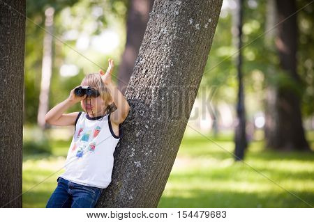 Portrait of a cute kid boy with binoculars on a sunny day. Curious child looking through the glasses while playing scouts in the park. Playing and exploring boy outdoors.