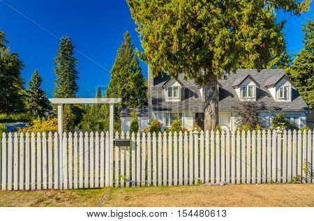 White wooden fence with green lawn and houses.