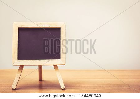 chalkboard with easel stand on wooden table in vintage tone