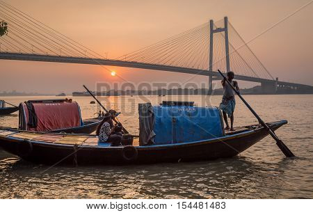 KOLKATA, INDIA - OCTOBER 11, 2016: A couple goes out on a boat ride from Princep Ghat Kolkata on the river Hooghly at sunset with the Vidyasagar Setu (bridge) at the backdrop.