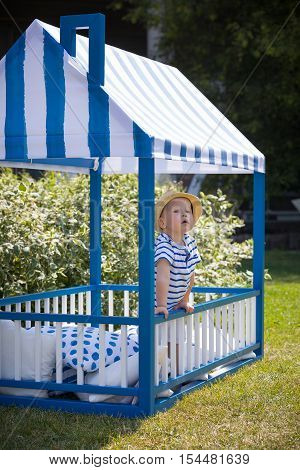 Adorable little toddler boy standing in the blue wood play bed house and looking out of the window. Child playing outdoors on a sunny day.