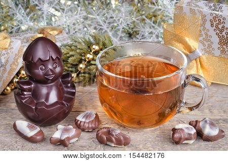 Christmas and a Cup of hot tea on old wooden background surface. Chocolate symbol of the year.