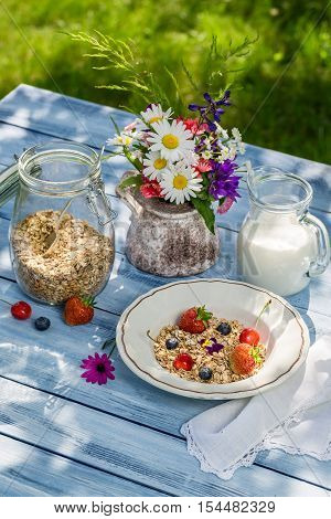 Breakfast with oatmeal fruit and milk on old wooden table