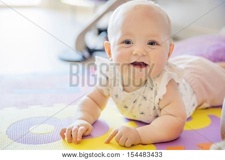 Happy baby girl with blue eyes playing on the floor with toys on a playmat. A cute young child plays and smiles.