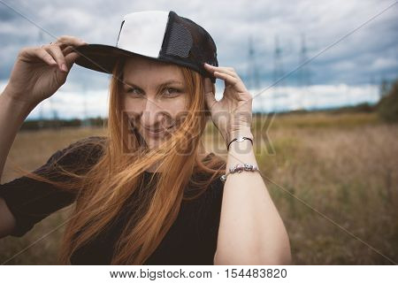 Young energy happy woman wears a cap hip-hop cap on yellow field with power pylons, close up, cloudy autumn