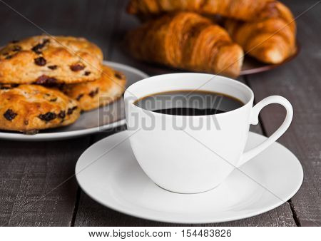 Cup of coffee with fresh scones and croissants on wooden table