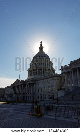 Backlit iconic view of the United States Capitol Building cupola and statue, on Capitol Hill in Washington DC, USA.