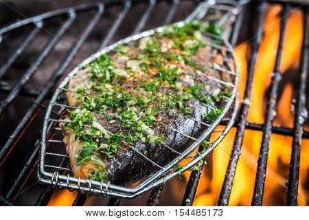 Closeup of grilled fish with spices on fire