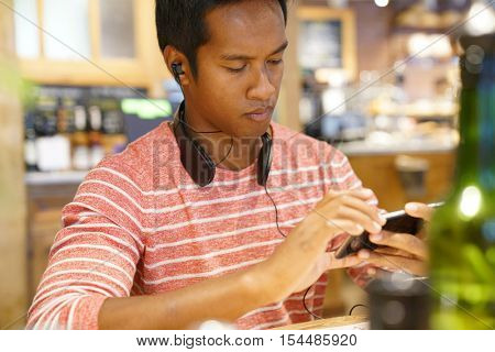 Man in coffee shop websurfing on smartphone