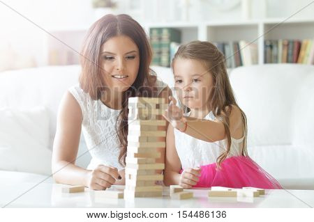 Portrait of a mother and daughter playing board game