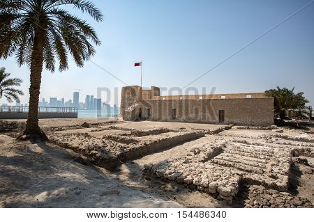 MUHARRAQ, BAHRAIN - OCT 29, 2016: Beautiful view of the Bu Maher Fort in Arad with its ruins in the foreground, along with Manama city in the hazy background