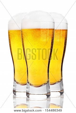 Glasses of cold beer with foam and froth on white background