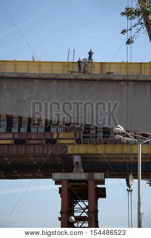 Two workers in workwear standing high on a bridge processing construction work