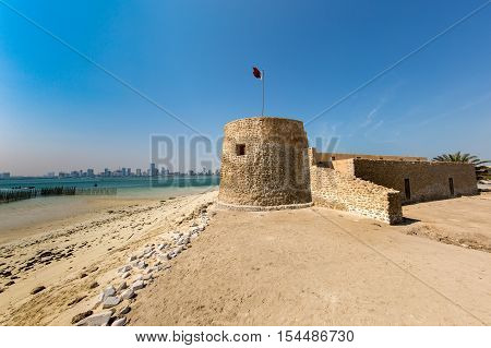 MUHARRAQ, BAHRAIN - OCT 29, 2016: Beautiful view of the Bu Maher Fort in Arad with the beach and Manama city in the hazy background
