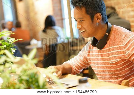 Young man sitting in restaurant websurfing on tablet