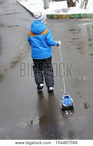 A small child (avid rear) which stands on the wet pavement and holds the rope toy car. The machine all in the snow. A child just walked through the snow.