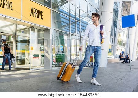 Happy young man arrived from trip. He is walking from airport with luggage and smiling. Guy is looking back and smiling